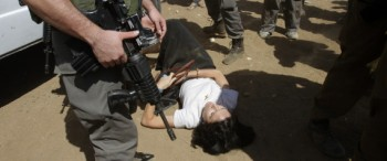 French diplomat Castaing lays on the ground after Israeli soldiers carried her out of her truck in the Jordan Valley