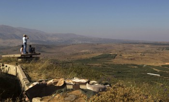 A man uses binoculars as he looks towards Syria from part of an abandoned military outpost in the Golan Heights